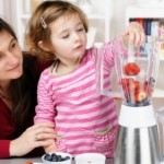 mom and daughter make smoothie cropped