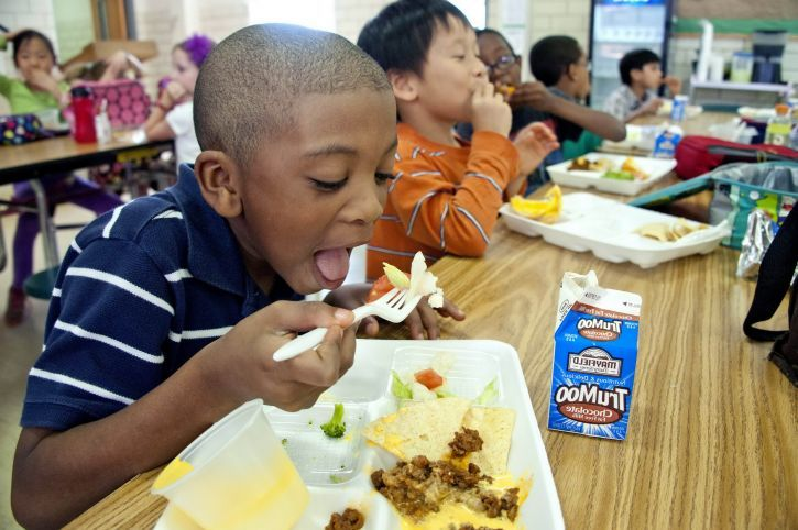 Children eating lunch in a lunch room, focused on boy eating vegetables and drinking chocolate milk