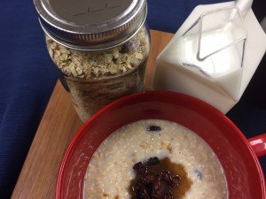 Oatmeal in a red mug with a glass container of milk and a glass container of oats