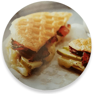 Sandwich with waffle pressed bread and bacon on a white plate
